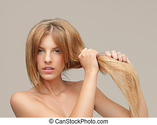 upset woman pulling dry hair split ends - young woman...