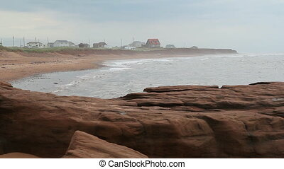 Misty beach - Misty beach on grey day with red rocks in the...