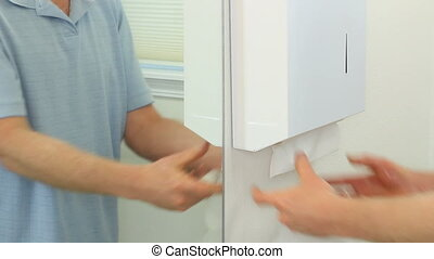 Drying Hand Skin in a Restroom - Man drying wet hands with a...