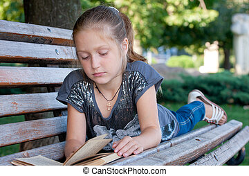 reading at the park - little girl sitting on a bench at the...