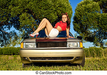 young sexy woman lay on car bonnet