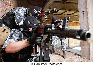 Soldiers in masks aiming the target with guns