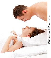 Man looking down on woman laying in bed - Young man looking...