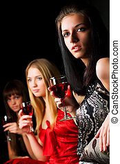 Young women in a night bar - Three young women drinking red...