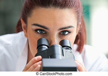 Close up of a scientist posing with a microscope in a...
