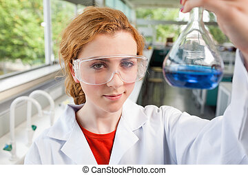 Science student holding a flask with protective glasses