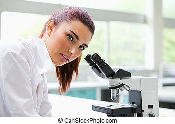 Brunette posing with a microscope while looking at the...