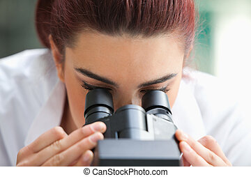 Close up of a scientist looking into a microscope