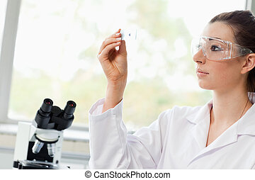 Beautiful science student looking at a microscope slide