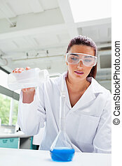 Portrait of a female science student pouring liquid