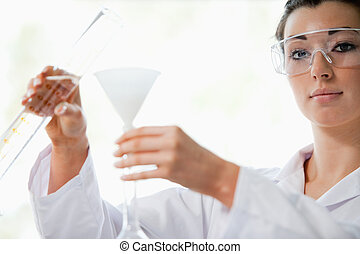 Scientist pouring liquid in a funnel while looking at the...