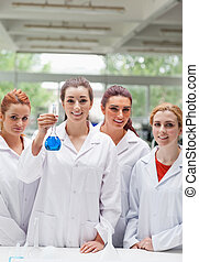 Portrait of lab partners posing with a flask smiling at the...