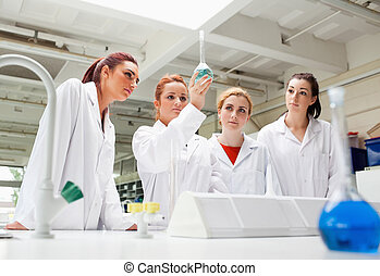 Science students looking at a liquid in a flask