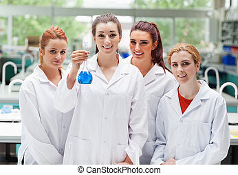 Lab partners posing with a flask looking at the camera