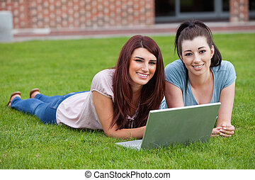 Friends using a notebook while lying on the lawn