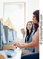 Portrait of smiling students using computers