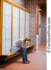 Portrait of a lonely student sitting in a corridor