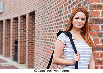 Smiling student standing up outside a building