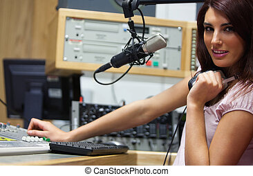 Radio host setting the sound while looking at the camera