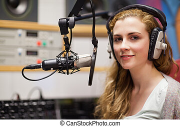 Young woman posing with a microphone in a studio