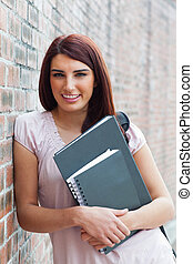 Portrait of a happy student holding her binders