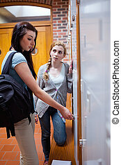 Portrait of student opening her locker while speaking with her friend in a corridor