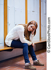 Portrait of a sad student sitting on a bench looking at the...