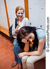 Student making fun of her classmate in a corridor