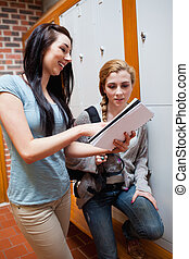 Portrait of a student showing her notes to her friend