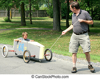 Senior pulling a go-cart containing his grandson