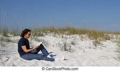 Woman Reading On Dune - Woman reads and studies her bible on...