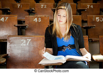 College Girl with Text Book - Young college girl looking at...
