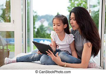 Mother and daughter with digital tablet - Cute little girl...