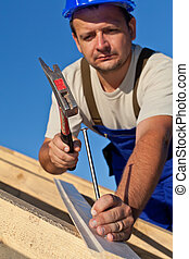 Carpenter working on the roof driving a nail in - shallow...