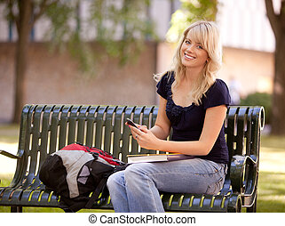 Attractive Student Sending Text Message - Friendly young...