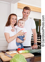 Family at Home in Kitchen - Portrait of a happy young family...