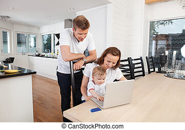 Laptop lessons - Family working on laptop together at home
