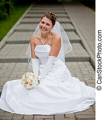 fiancee is sitting on the street, laughing - Bride sitting...