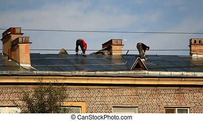 Roof repairs - Two roofers working on the roof