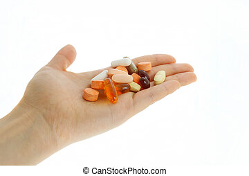 Hand holding lots of supplements