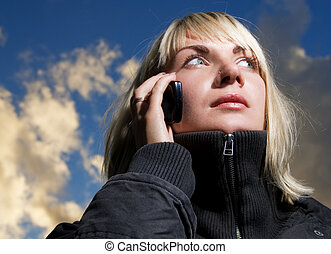 Girl talking on the phone over blue cloudy sky
