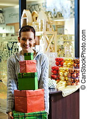 Teenager girl with gift boxes in a shop