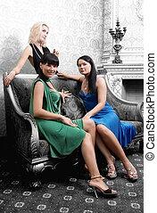 Three beautiful girls in luxury monochrome interior