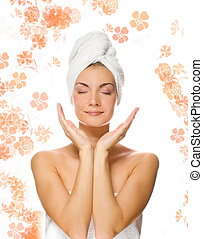 Young lovely lady applying moisturizer to her face after shower