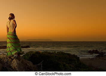 Beautiful girl relaxing near the sea at sunset time