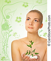 Beautiful blond girl holding young plant growing up through stones on abstract floral background
