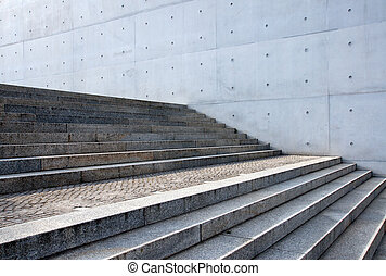 Grey stairs in front of a wall