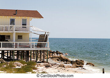 House Beach Erosion - Beach house damaged by wave action and...