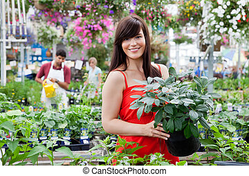 Beautiful female customer holding potted plant with workers...