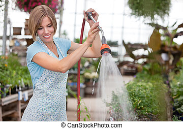 Attractive woman watering the plants - Young attractive...